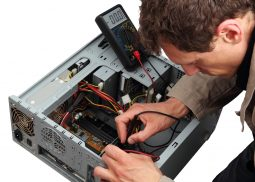 Professinal repairing a PC with measuring instrument